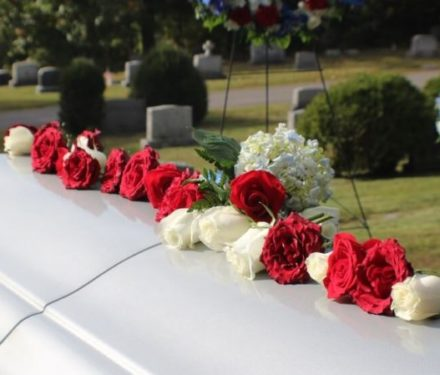 White Coffin with Red and White Roses at a Funeral